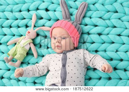 Cute little baby in bunny hat lying on soft knitted blanket