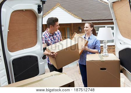 Young Couple Moving In To New Home Unloading Removal Van