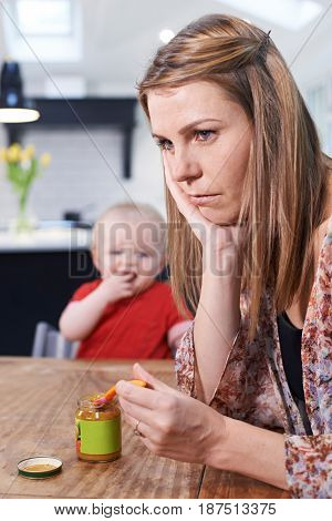 Stressed Mother Trying To Feed Fussy Baby