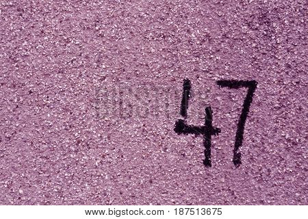 Number Fourty Seven On Purple Plaster Wall.