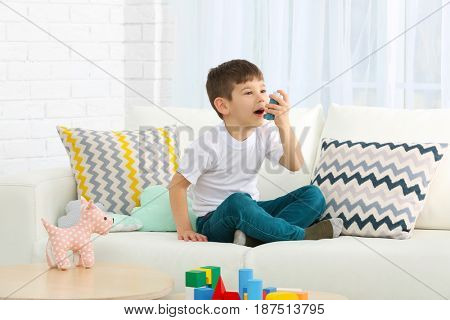 Cute little boy using inhaler at home. Allergy concept