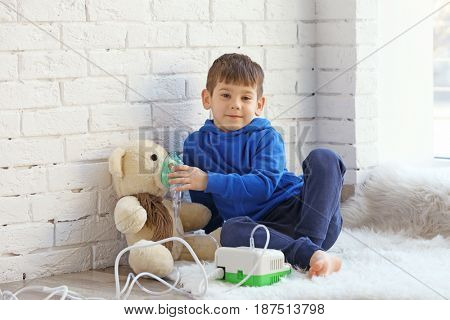 Little boy playing with toy bear and nebulizer while sitting on floor near window. Allergy concept