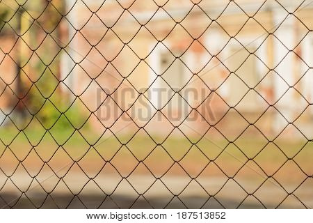 Metal mesh netting on the background of blurred buildings
