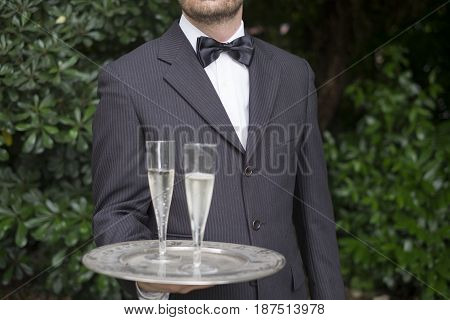 Waiter man serving champagne during a party