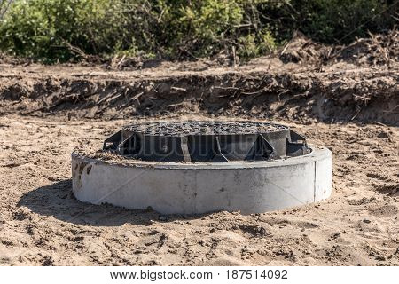 Iron and concrete sewer plate on a sandy construction site