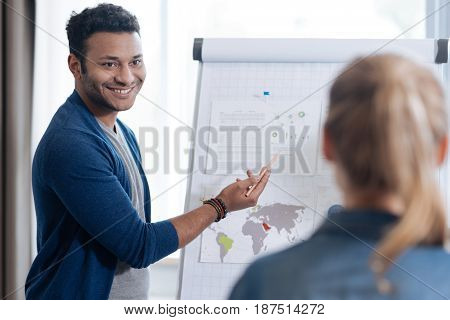 Business report. Happy joyful positive man standing in front of the flip chart and presenting his business report while holding a pencil