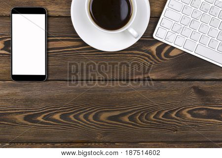 Office desk with copy space. Digital devices wireless keyboard mouse and tablet computer with empty screen on dark wooden table with cup of coffee top view
