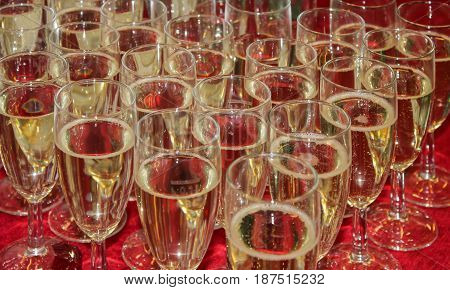 Glass wine glasses with champagne on a red tablecloth