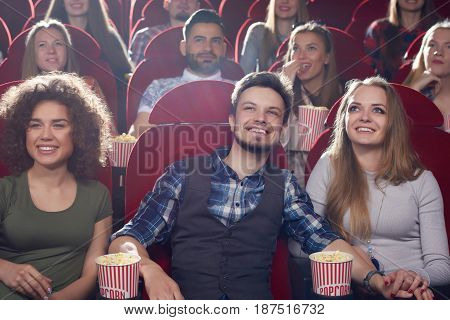 Front view of three smiling friends, two girls and one brunet man, spending free time together, watching movie in modern cinema hall. Group of boy and girlfriends looking at projector.