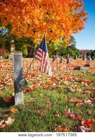 American veteran flag in autumn cemetery in New England