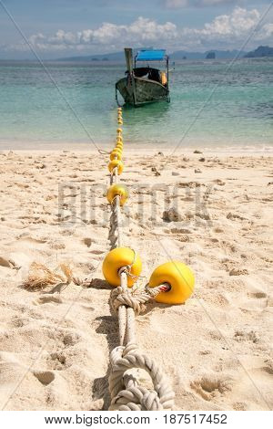 Close up Anchor rope anchor and boat in the beach