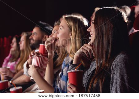 Big group of young best friends, stylish girls and boys watching funny film at cinema, spending free time together, eating tasty popcorn. Pretty and stylish women drinking cola, looking at big screen.