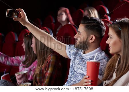 Couple of two best friends, handsome arabian man and caucasian pretty woman posing with cola, taking self portrait at smart phone in cinema. Boyfriend and girlfriend making photo in modern cinema hall.