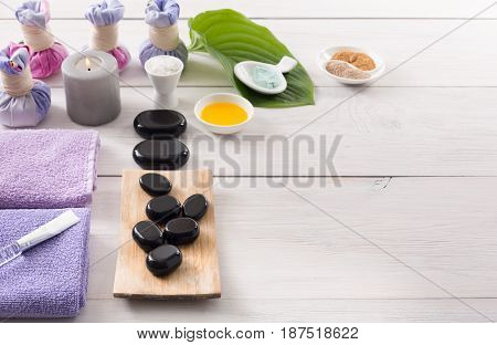 Spa treatment and aromatherapy concept background. Zen black stones, aroma salt, herbal balls for indian spa, candles, details and accessories for wellness beauty parlor. White wood with copy space