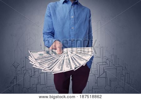 Young businessman holding large amount of bills with grungy drawings of a city and numbers behind him