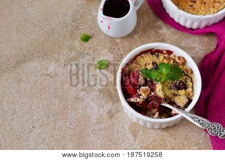 Crumble with berries oatmeal and nuts on a concrete background