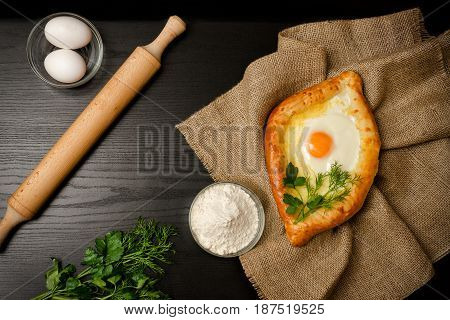 Georgian Cuisine. Top View Of Khachapuri On Sackcloth, Flour, Eggs And Rolling Pin. Black Table, Spa