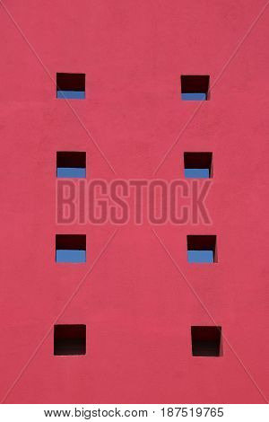 Red wall with sky through small windows