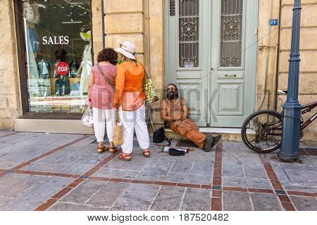 HERAKLION GREECE - JULY 09 2016: Crete. Joyful homeless man on a shopping street in the historic center of the city. Heraklion - the largest city on the island.