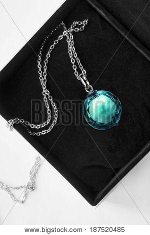 Large blue crystal ball pendant in black jewel box closeup