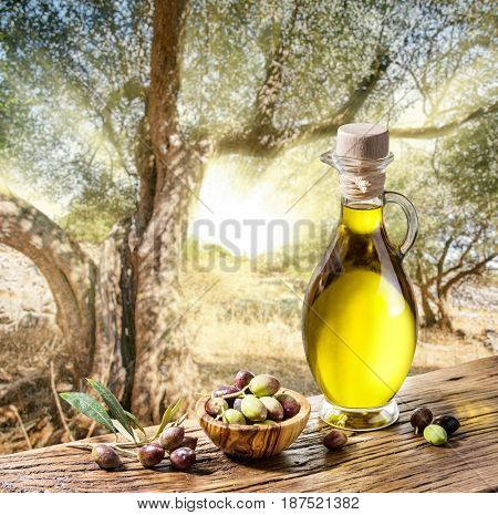 Olive berries in the wooden bowl and bottle of olive oil on the table. The beautiful sunset in the background.