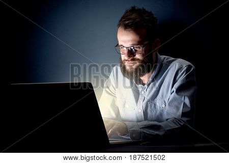 Young handsome businessman working late at night in the office with a dark background