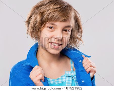 Emotional portrait of attractive caucasian little student girl with beautiful brown eyes. Funny cute smiling child looking at camera - close-up.