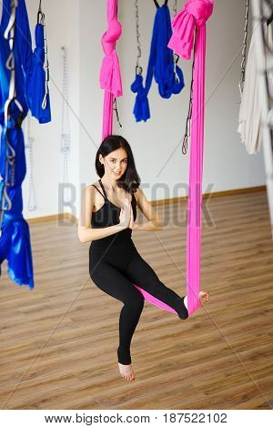 Young female person in pink hammock sits in position with attached hands and does aero yoga. Anti-gravity sport exercise, keeping balance on hanging material