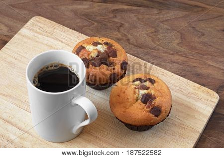 Cup of black coffee and muffins with chocolate on wooden board