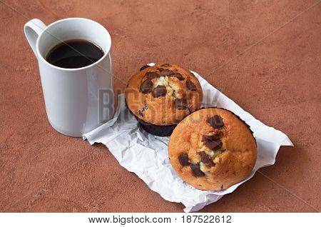 Muffins with chocolate and cup of black coffee
