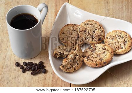 Plate in the shape of heart with chocolate cookies and black coffee on wooden table