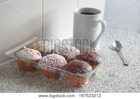 Cupcakes are different and a cup of black coffee on kitchen table