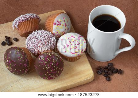 Cupcakes are different and a cup of black coffee on wooden cutting board