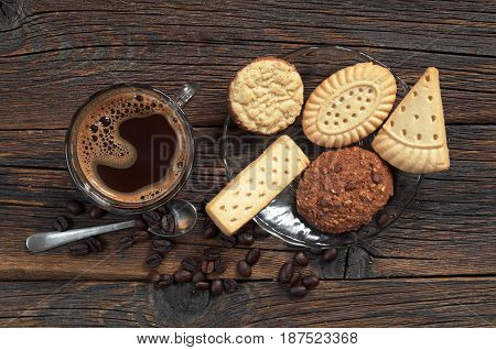 Different shortbread cookies and cup of hot coffee on old wooden background top view