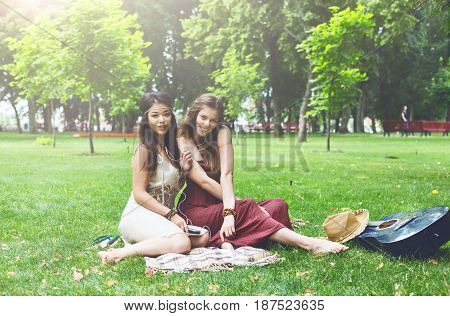 Fancy boho girls have picnic in park on grass. Modern hippie style