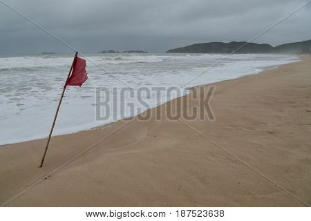 Red flag to alert the beach with dangerous waves in a raining day