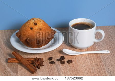 Cup of hot coffee and cupcake with raisins for breakfast on table