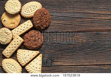 Mix of shortbread cookies on old wooden background top view. Space for text