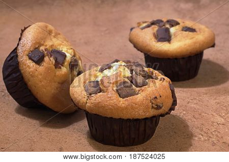 Fresh muffins with chocolate on brown background
