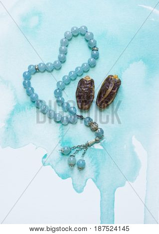 Beautiful background for Ramzan or Ramadan.  Ripen date fruits with an Islamic prayer beads on an artistic background. 'Ramadan Kareem' symbolic image.