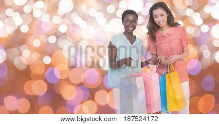 Digital composite of Happy women carrying shopping bags over bokeh