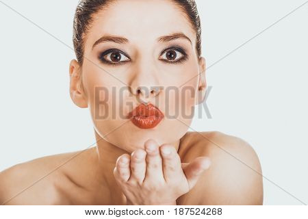 Beautiful woman with make up blowing a kiss.