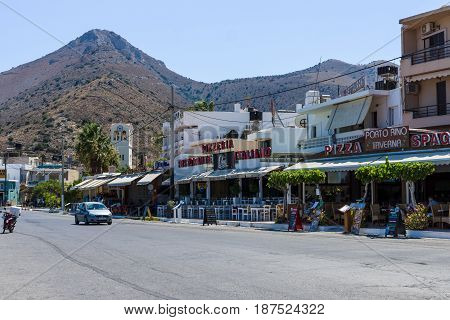 CRETE GREECE - JULY 11 2016: The embankment of a coastal elite tourist town Elounda on the Greek island of Crete municipality of Agios Nikolaos. View from the sea.
