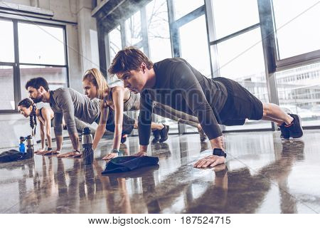 Group Of Athletic Young People In Sportswear Doing Push Ups Or Plank At The Gym, Group Fitness Conce