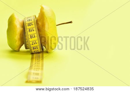 Tape For Measuring Ties Around Bitten Apple On Yellow Background