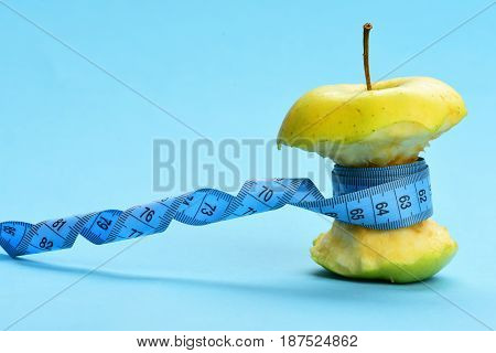 Blue Twisted Measuring Tape Holding Green Bitten Apple