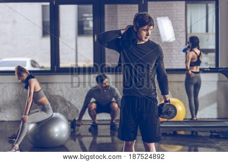 Athletic Tired Sportsman With Dumbbell At The Gym, Gym Workout Concept