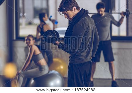 Athletic Young Sportsman Exercising With Dumbbell At The Gym, Gym Workout Concept