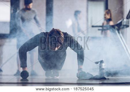 Athletic Young Sportsman Doing Push Ups With Dumbbells At The Gym, Gym Workout Concept
