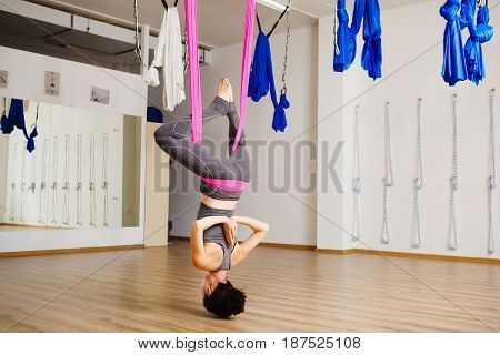 Woman hangs upside down doing aero anti gravity yoga exercises. Aerial antigravity pose, girl does exercises, meditate in calm position trying to achieve peaceful state of mind and body